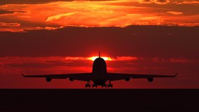 Large passenger airplane taking off and flying towards scenic orange sunset. Suitable as an iillustration for tourism, holidays, vacation, success, business and transportation concept video