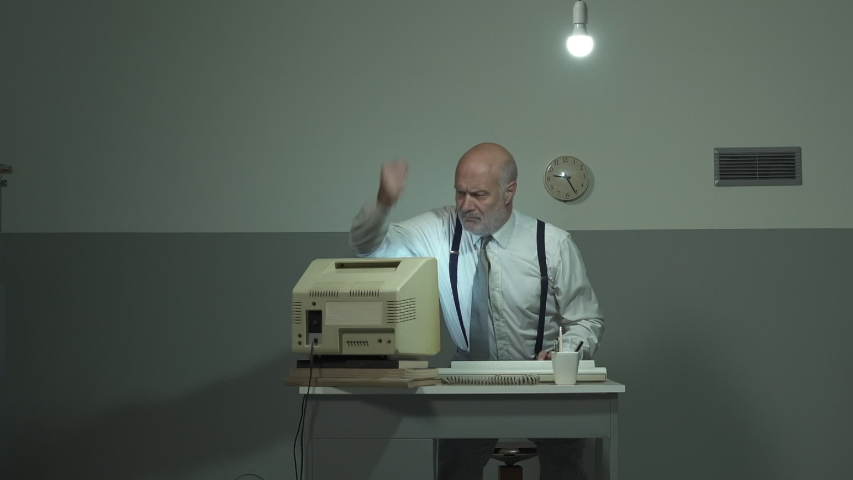 Angry mature businessman sitting at desk and hitting his outdated old computer
