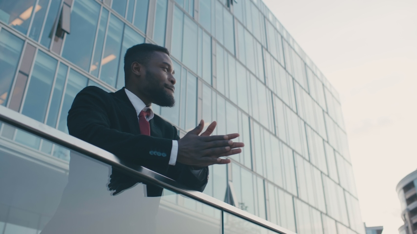 Young handsome black businessman dreaming and rubbing his hands in anticipation of a successful deal feeling good. Portrait of african american man on background of modern business center | Shutterstock HD Video #1039231994