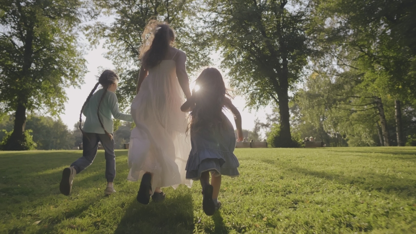 Young mother with siblings daughters together running towards sun having fun in city park garden. Family run on green grass at background of trees during summer sunset. Motherhood childhood concept