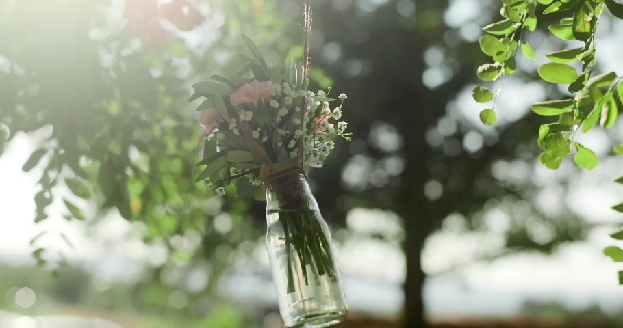 Bouquet of flowers in a glass bottle hangs on a tree. Wedding decor at an exit ceremony  | Shutterstock HD Video #1039235177