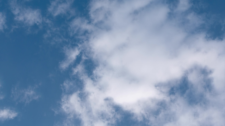 White clouds at the blue sky (bottom view). Fluffy white clouds fly diagonally at the blue sky background, as if you raised your head up. Time-lapse.  Royalty-Free Stock Footage #1039240817
