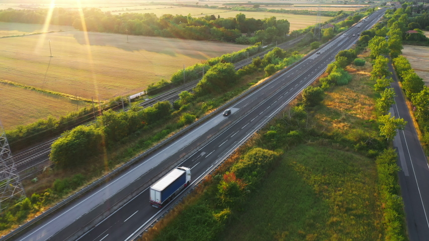 Aerial Drone Footage: Long Haul Semi Trucks Driving on the Busy Highway in the Rural Region of Italy. Agricultural Crop Fields and Hills in the Background Royalty-Free Stock Footage #1039245149