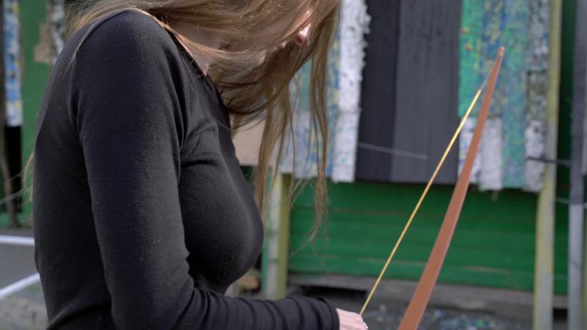 A girl shoots from a bow at targets. Archery sports, outdoor training. Wooden bow and arrow, accuracy, hitting the target. Evening light. Female focusing to the target.  #1039250114
