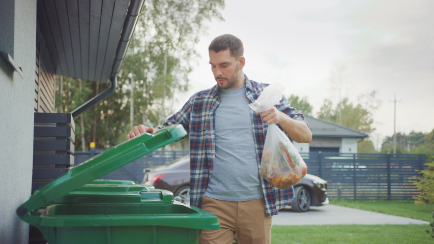 Caucasian Man is Walking Outside His House in Order to Take Out Two Plastic Bags of Trash. One Garbage Bag is Sorted into Biological Food Waste, Other is Thrown into Recyclable Bottles Garbage Bin. Royalty-Free Stock Footage #1039252367