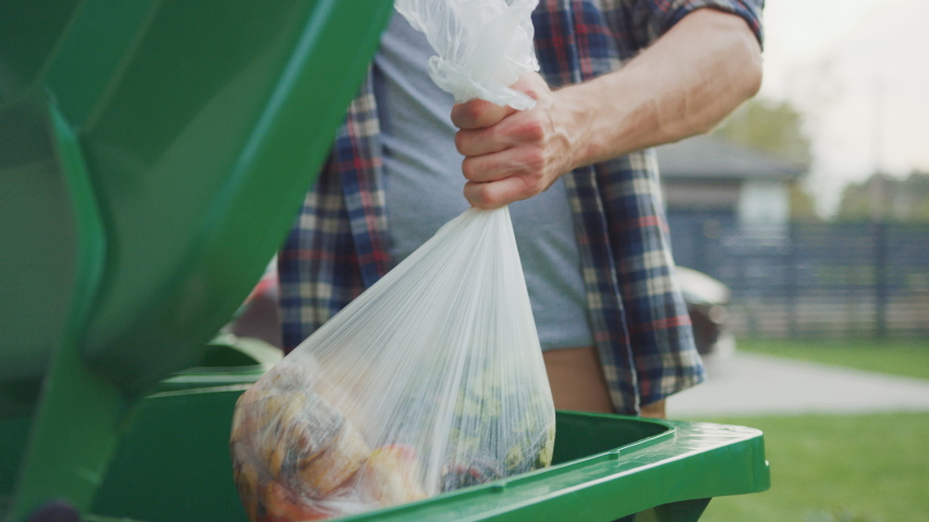 Close Up Shot of a Caucasian Male in Checkered Shirt Throwing Away Biological Food Waste into a Green Trash Bin. He Uses Correct Garbage Bin Because He is Sorting Waste and Helping the Environment.