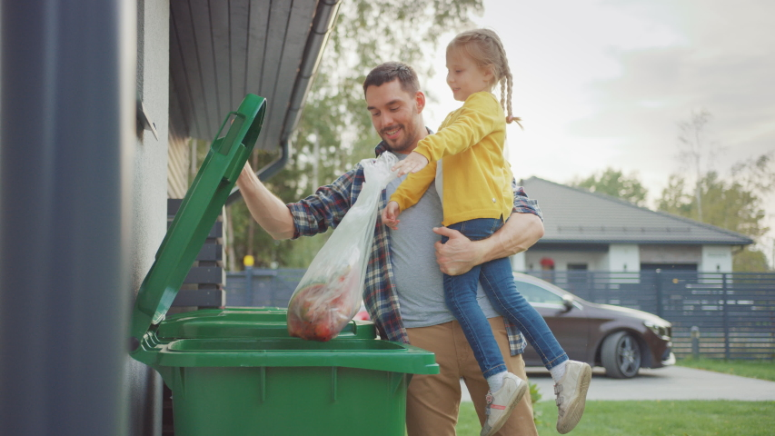Happy Father Holding a Young Girl and Going to Throw Away an Empty Bottle and Food Waste into the Trash. They Use Correct Garbage Bins Because This Family is Sorting Waste and Helping the Environment.