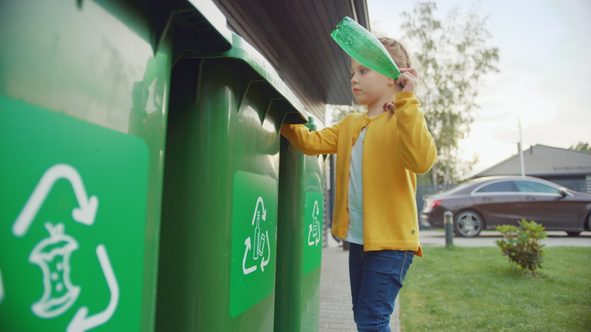 Young Girl is Walking Outside Her House in Order to Throw Away an Empty Plastic Bottle into a Trash Bin. She Uses Correct Garbage Bin Because This Family is Sorting Waste and Helping the Environment.