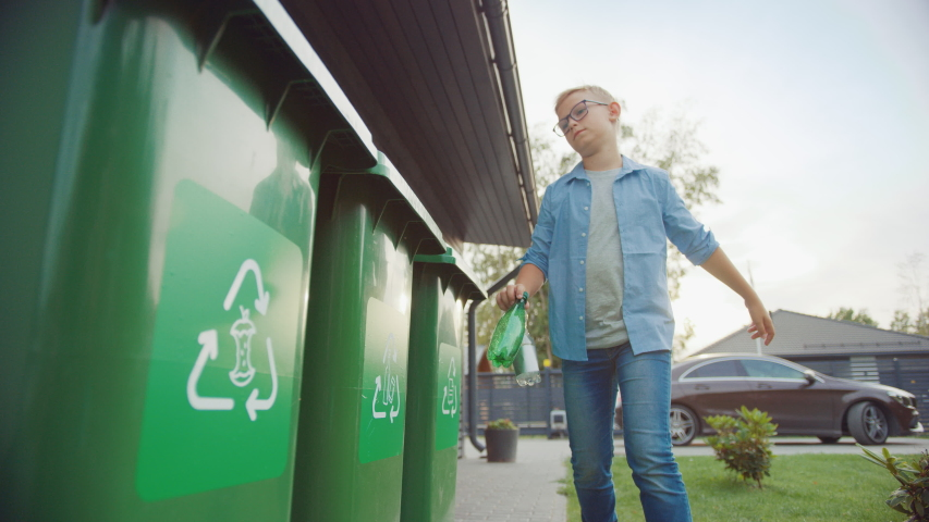 Young Boy is Walking Outside His Home in Order to Throw Away Two Empty Plastic Bottles into a Trash Bin. He Uses Correct Garbage Bin Because This Family is Sorting Waste and Helping the Environment.