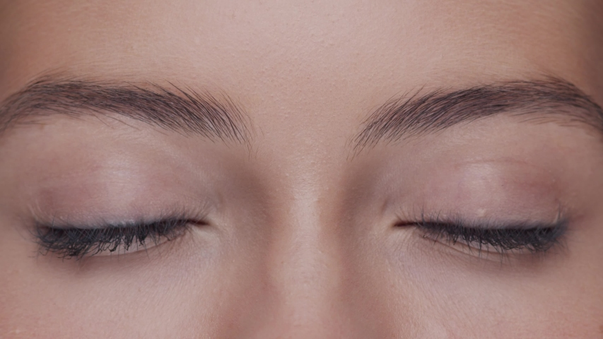 Close-up portrait of young, beautiful and natural woman opening her eyes. Face lifting, cosmetics and make-up.