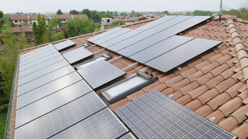 Solar energy panels installed on home residential rooftop, slow parallax circle aerial shot of domestic photovoltaic panel. Sustainable and renewable source of clean energy icon