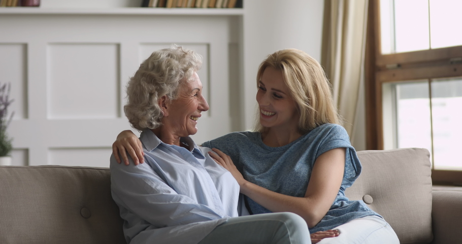Happy young grown daughter embrace old senior mother having fun conversation enjoy talk in house, two generation women family elder mom and adult woman laugh bonding chatting relax on sofa together