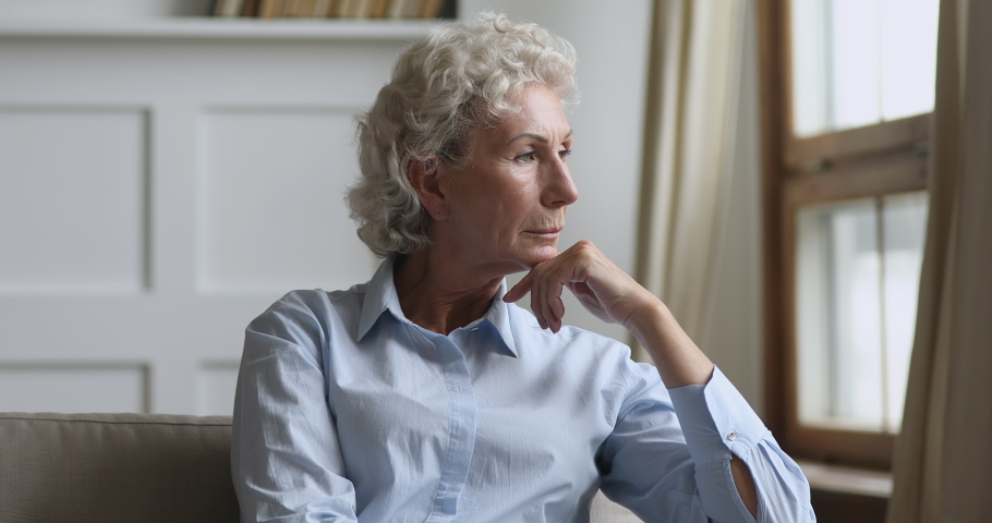 Serious thoughtful elderly old woman looking away sit on sofa alone think of loneliness problem, pensive sad senior middle aged grandma feel worried depressed lonely at home from anxiety and solitude