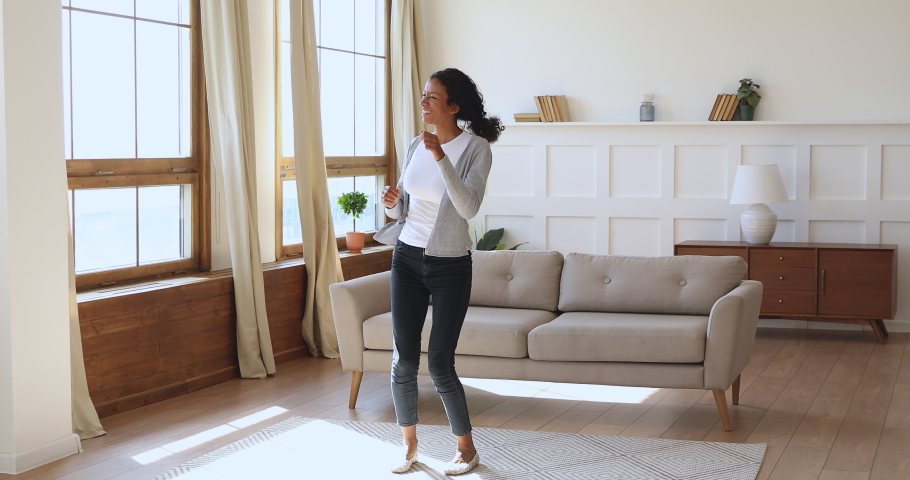 Funny carefree mixed race woman dancing alone laughing having fun at home, happy positive joyful african lady listening music moving enjoying freedom and active lifestyle in living room interior | Shutterstock HD Video #1039317560