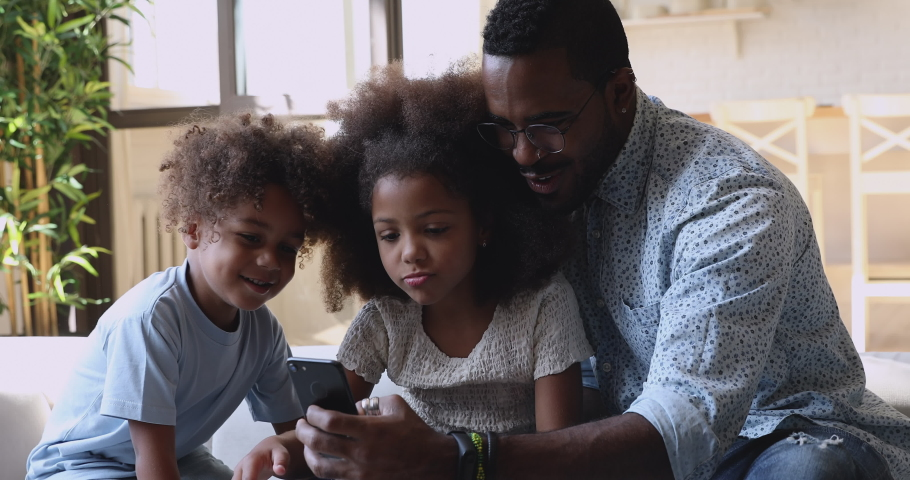 Happy african family dad and little kids son daughter sit on sofa laughing having fun holding using mobile phone apps watching funny social media video, taking selfie looking at cell screen at home
