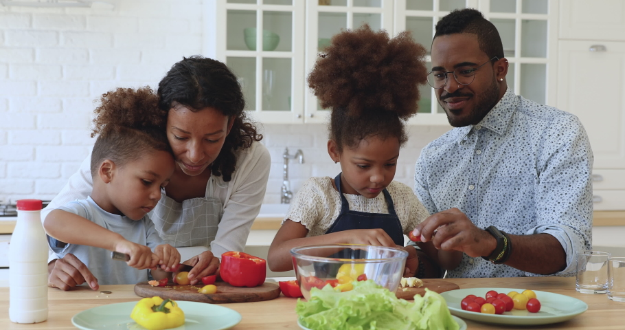 Cute little african american boy and girl help parents cutting fresh vegetables tomatoes pepper for healthy salad, happy mixed race family mom dad and kids girls cooking together in modern kitchen
