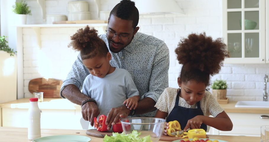 Young happy african father dad teach cute small kids siblings hold knife cut fresh vegetable salad in kitchen explain little children son daughter learn cook prepare healthy food together at home.