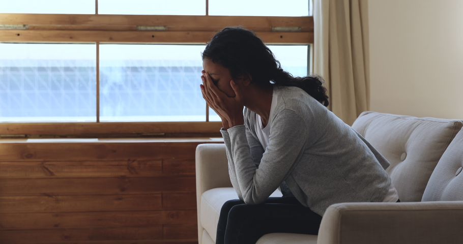 Depressed worried young african american woman in trouble feeling upset frustrated anxious regret abortion thinking of psychological problem suffer from anxiety concept sit on sofa at home alone.