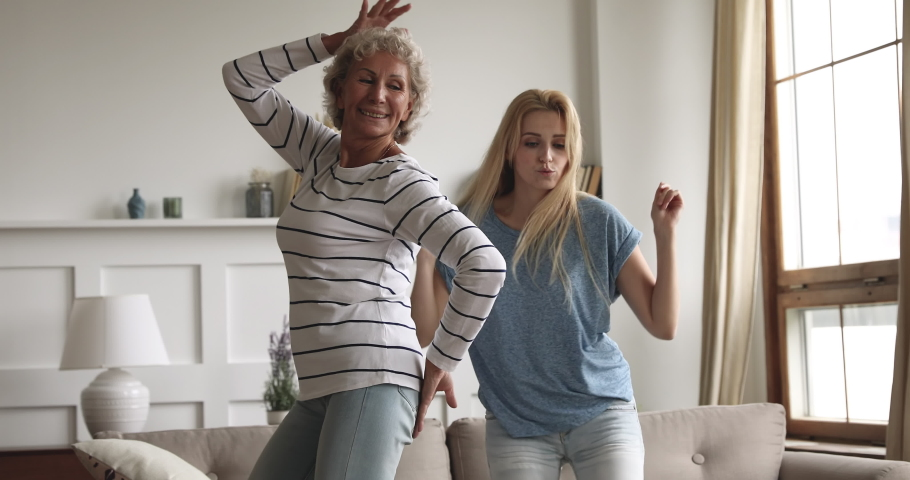 Happy carefree two age generation women family young grown adult daughter and healthy active old senior mature mother listening music dancing together laughing having fun at home in living room