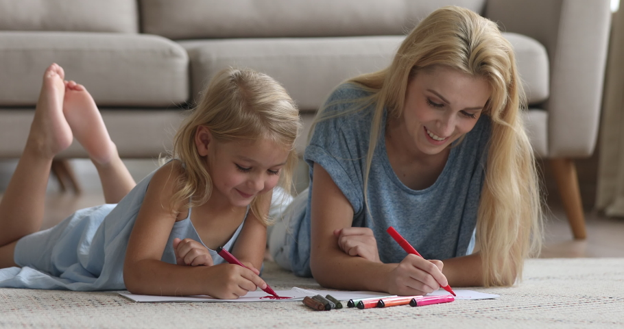 Cute smart preschool child daughter learning drawing with felt pen coloring picture talk enjoy creative activity with young mom or babysitter helping little kid girl lying on floor playing at home.
