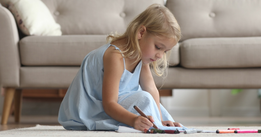 Cute small kid girl artist playing alone drawing coloring picture with felt pen sit on floor, focused smart preschool child enjoying creative art hobby activity at home, children development concept