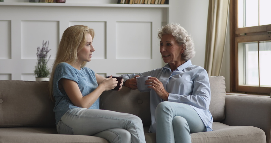 Young adult grown daughter talking to old middle aged mother gossiping having trust understanding conversation at home, happy two women generation family chatting drinking coffee sit relax on sofa