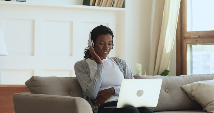 Happy young african woman wear wireless headphones make video call online chat look at laptop screen sit on sofa, smiling girl talk to webcam communicate by internet computer conference app at home Royalty-Free Stock Footage #1039317809