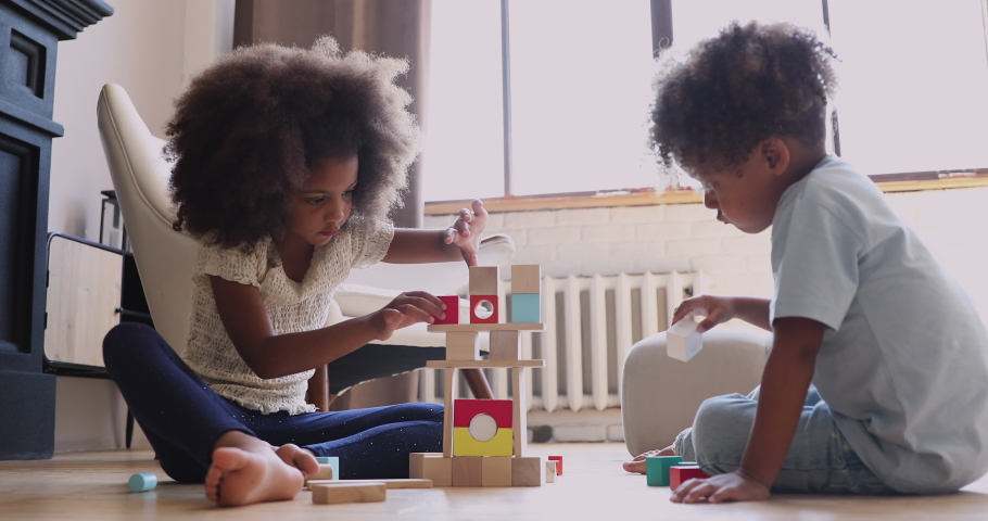 Two cute little african children siblings play with wooden blocks on warm heated floor at home kindergarten, small mixed race kids boy and girl building castle of toys, children development concept