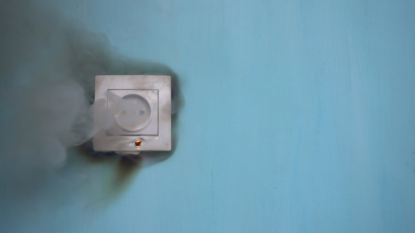 Apartment fire is caused by electrical outlet faults. Burnt and damaged electric plug socket from overload short circuit.