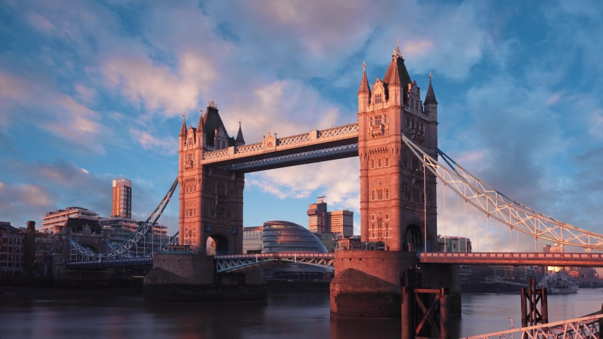 A beautiful scene showing the famous London, England landmark of Tower Bridge during a winter morning sunrise. Colorful time lapse with dramatic, interesting clouds. | Shutterstock HD Video #1039329494