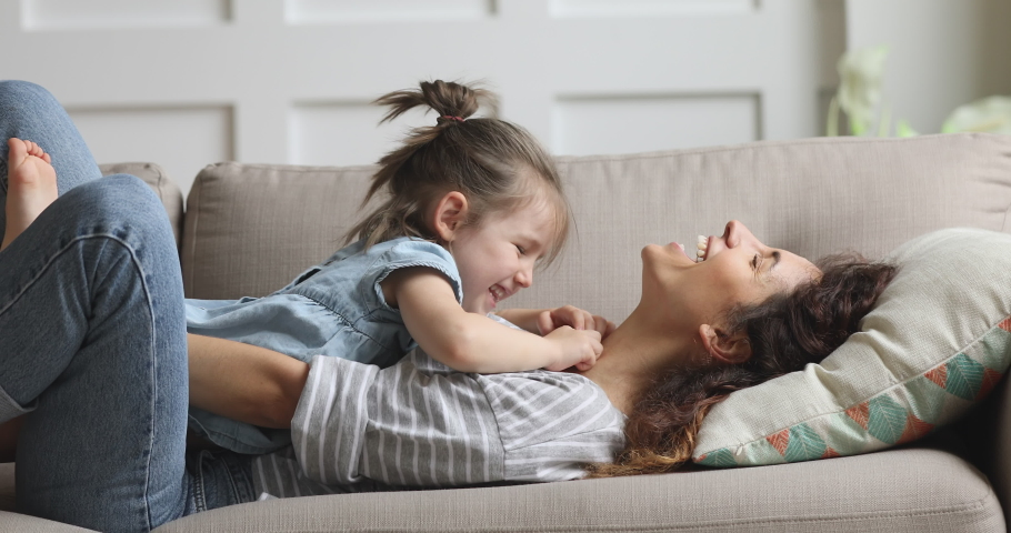 Happy carefree mother and cute small child daughter tickling laughing having fun lying on sofa and playing, smiling mum enjoying bonding cuddling hugging spending time with little funny kid at home #1039337837