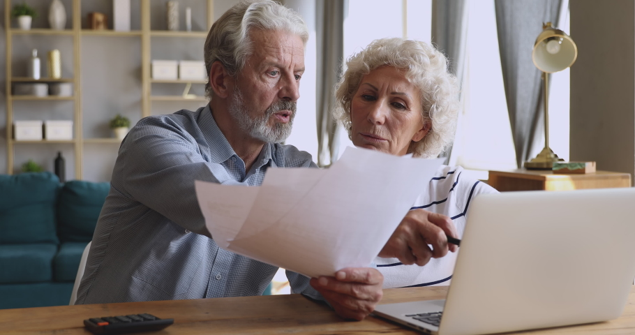Worried senior retired couple checking calculating bills bank loan payment doing paperwork discuss unpaid debt taxes, stressed old grandparents family look at laptop upset about money problem concept | Shutterstock HD Video #1039337867