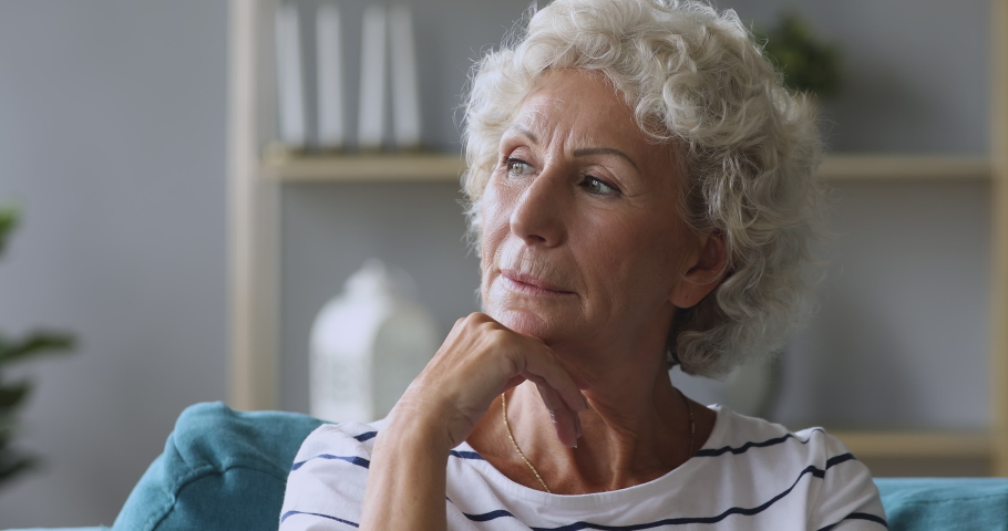 Pensive thoughtful lonely senior lady serious face looking away sitting alone on sofa at home, worried melancholic single old elder woman grandmother waiting thinking of solitude loneliness concept | Shutterstock HD Video #1039337873