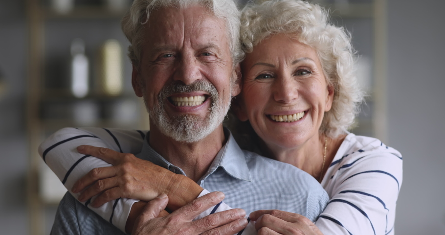 Cheerful old elderly adult family couple hugging laughing bonding looking at camera, smiling healthy senior retired grandparents husband and wife happy faces embracing at home, close up portrait