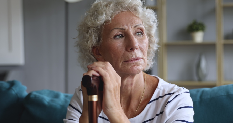 Depressed thoughtful elderly adult woman holding walking cane stick sit alone on sofa, pensive sad old senior grandma feeling lonely suffer from geriatric health problems concept, close up view