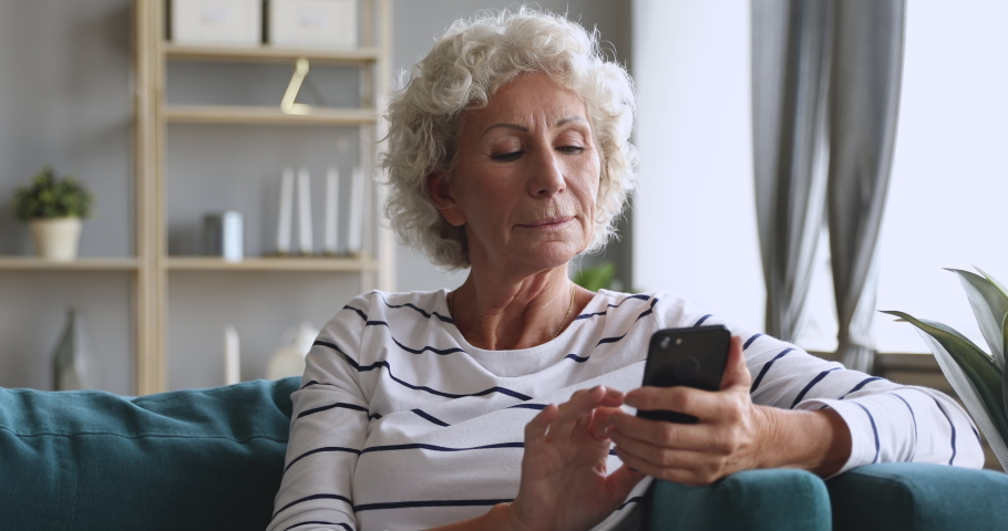 Older grey haired grandma enjoy using mobile app sit on sofa, senior lady texting typing message hold smart phone look at cellphone screen browsing social media at home, old people tech users concept Royalty-Free Stock Footage #1039337927