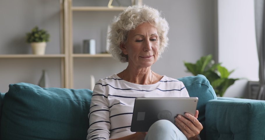 Smiling senior old adult woman using digital tablet computer technology relaxing on sofa, happy retired elderly adult grandma holding electronic pad browsing internet, read e book in app at home