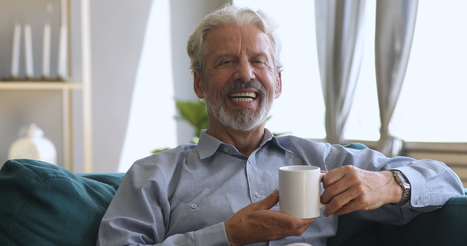 Happy elderly senior man with wide dental smile sitting on sofa holding hot drink cup, positive old grandfather relaxing alone at home drinking tea looking at camera laughing posing for portrait