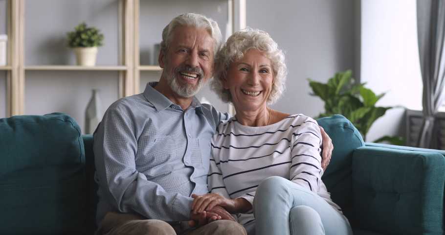 Serious happy senior elderly family couple bonding looking at camera hold hands sit on sofa, smiling old adult grandpa husband embrace grandma wife on couch at home, retired grandparents portrait #1039337987