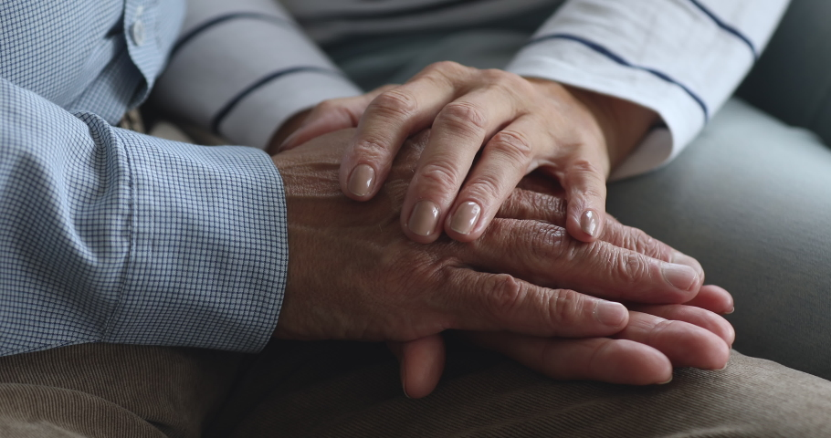 Caring elderly grandma wife holding hand supporting senior grandpa husband give empathy care love, old married grandparents couple together two man and woman hope understanding concept, close up view