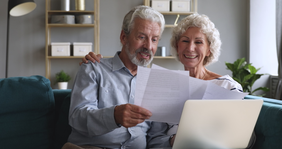 Happy old couple talking checking papers holding domestic bills and laptop computer, satisfied bank clients senior grandparents customers planning budget investment loan insurance payment at home