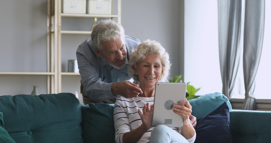 Smiling senior old couple talking using digital tablet computer modern tech at home on weekend lifestyle, happy elderly grandmother and grandfather doing internet shopping choose sale offers together Royalty-Free Stock Footage #1039338020