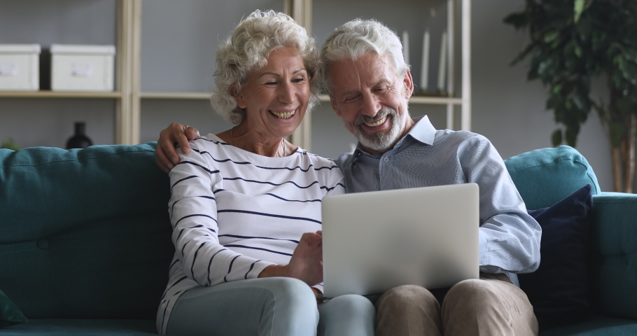 Happy old retired couple talking laughing using laptop doing internet shopping choose sale offers together, senior elderly family grandparents relaxing looking at computer screen sit on sofa at home