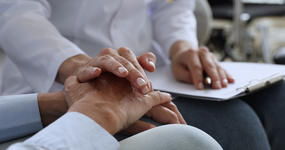 Young woman doctor nurse hold hand of elderly female grandma patient at home hospital visit give support help and comfort concept, medical care responsibility, senior people healthcare, close up view