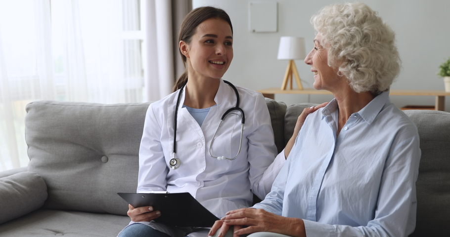 Caring young female nurse caretaker doctor helping talking with senior grandmother patient give support empathy encouraging elderly woman at medical visit, older people healthcare recovery concept