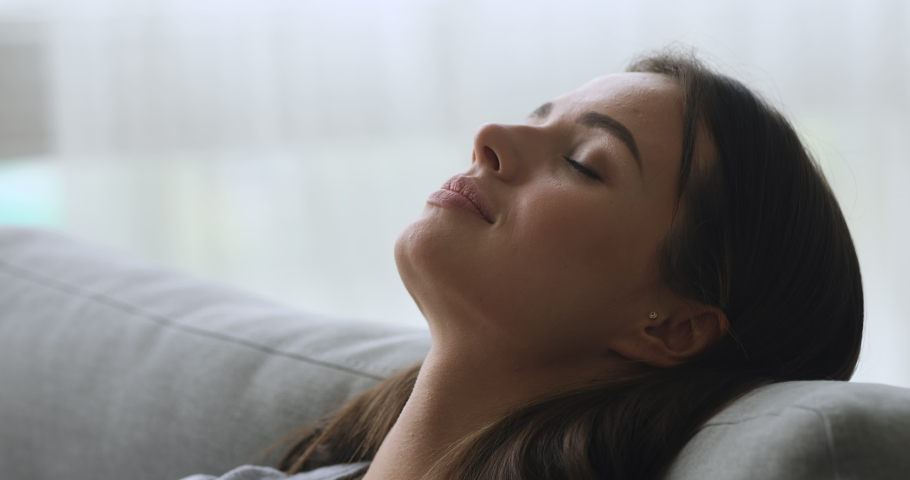 Healthy calm tired attractive young woman serene face relax on comfortable sofa taking deep breath of fresh air rest on couch enjoy welfare peace of mind and no stress concept at home, close up view Royalty-Free Stock Footage #1039338113