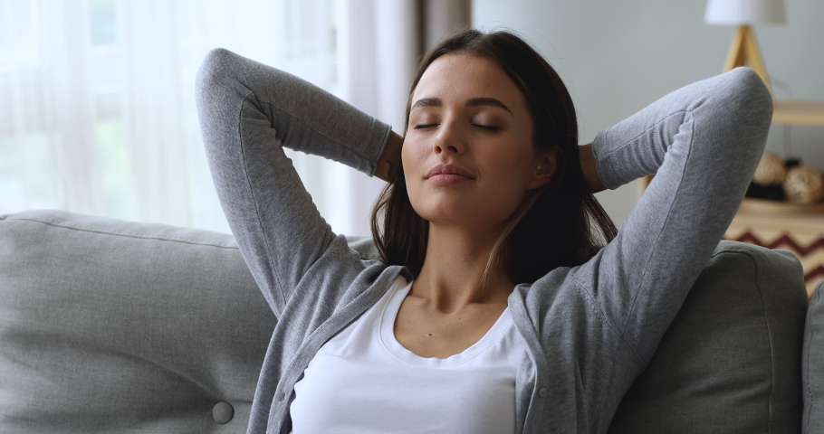 Serene attractive young woman resting on couch taking deep breath of fresh air holding hands behind head, healthy calm lady relaxing on comfortable sofa napping feel stress free at home lounge alone