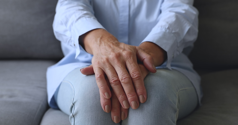 Old senior woman sit on sofa alone with hands folded, lonely elderly mature grandmother patient having health care arthritis problem suffer from loneliness poverty depression concept, close up view | Shutterstock HD Video #1039338149