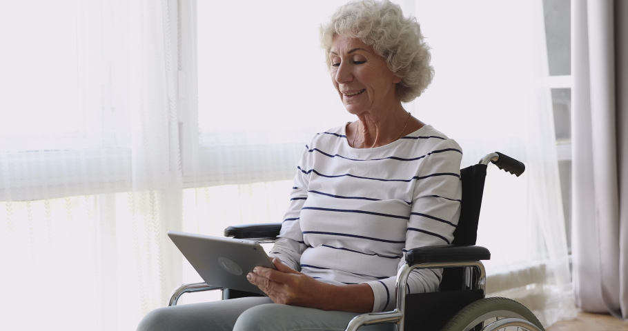 Happy disabled senior adult retired woman sitting on wheelchair holding digital tablet at home, smiling elderly grandma enjoying using online apps browsing internet, older people and tech concept
