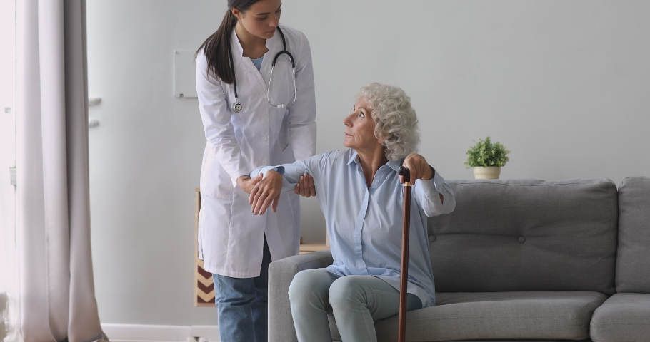 Young woman nurse caregiver help disabled old senior grandmother patient hold cane stick in retirement house, female doctor carer provide elderly lady medical service, older people healthcare concept